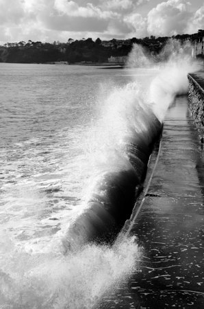 Waves crashing on Dawlish Sea Wall in black and white