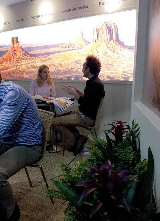 man and woman sitting at table at travel trade show