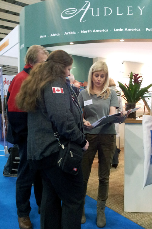 Woman explaining holiday options to a couple at a travel trade show