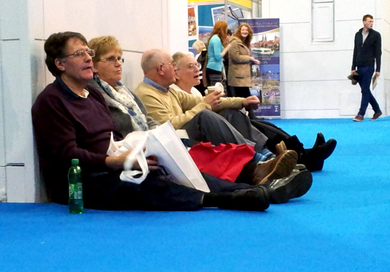 Worn out visitors take a break at a travel trade show