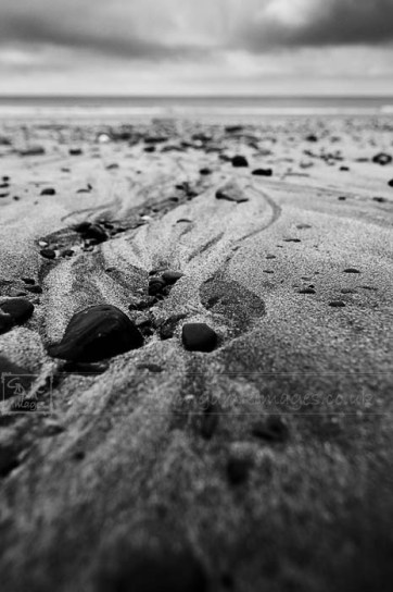 Low angle view of a pebbly beach in black and white