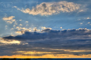 HDR sun rays over the top of and through gaps in clouds
