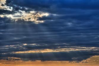 HDR Sun rays shining through gap in clouds