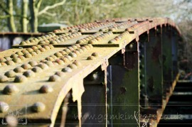 Rusting disused railway bridge over the Ashby canal